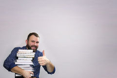 Student adult beard man with stack of book in a library Royalty Free Stock Images