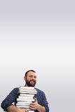 Student adult beard man with stack of book in a library royalty free stock image