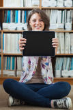 Student against bookshelf holding out tablet PC on the library floor Stock Photos