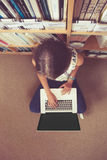 Student against bookshelf using laptop on the library floor Royalty Free Stock Photo