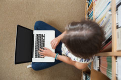 Student against bookshelf using laptop on the library floor Stock Photography