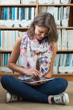 Student against bookshelf using tablet PC on the library floor Stock Image