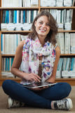 Student against bookshelf using tablet PC on the library floor Stock Photography