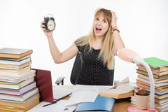 Student with an alarm clock in hands understand that slept exam. A student with an alarm clock in hands understand that slept exam Stock Image