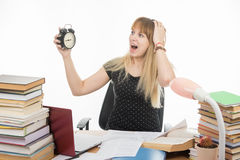 Student with an alarm clock in hands understand that slept exam and screaming looking at his watch. A student with an alarm clock in hands understand that slept Royalty Free Stock Images