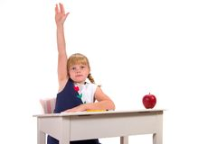 Student with Answer or Question. Young female student with hand raised for answer or question sitting at desk with apple Royalty Free Stock Photos