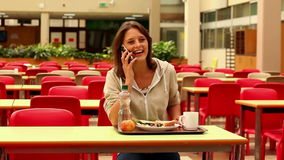 Student answering her phone while having lunch in canteen Royalty Free Stock Photo