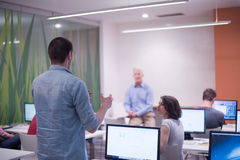 Student answering a question in classroom. Mature teacher and students in computer lab classroom Stock Images