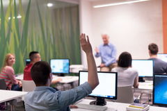 Student answering a question in classroom. Mature teacher and students in computer lab classroom Stock Image