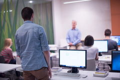 Student answering a question in classroom. Mature teacher and students in computer lab classroom Royalty Free Stock Photo