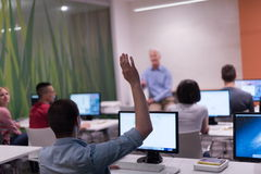 Student answering a question in classroom. Mature teacher and students in computer lab classroom Royalty Free Stock Image