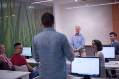 Student answering a question in classroom. Mature teacher and students in computer lab classroom Royalty Free Stock Photography