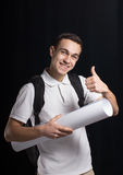 Student architect. A happy student.He smiles us.He weared a white t-shirt. He keeps a book and architectural sheet of paper.He has a bag behind.His smile shows Royalty Free Stock Photo