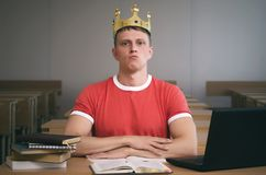 Student. Arrogant student boy with golden crown above his head with an insolent look sits at a desk. Bad behavior in school concept royalty free stock images