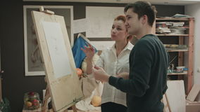 Student and art teacher during painting lesson stock video footage