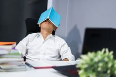 Student asleep in desk with book on his face. Student asleep in the desk with book on his face Royalty Free Stock Images