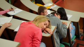 Student asleep at desk in lecture hall stock footage