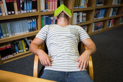 Student asleep in the library with book on his face Stock Photos