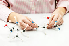 Student assembling molecule models. Hand of female student assembling amino acid molecule models for science project Stock Photo