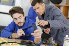 Student with auto part studying automotive trade in vocational school. Apprentice stock photo