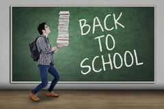 Student back to school and carrying a pile of books. Male high school student back to school and walking in the classroom while carrying a pile of books Stock Images