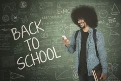 Student with back to school text and doodle. College student looking at smartphone while standing with back to school text and doodle on chalkboard Stock Photography