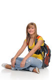 Student with backpack. Young student woman carrying a backpack and smiling sitting on the floor stock photos