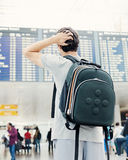 Student with backpack in airport. Back view of confused college student traveling with backpack, standing with hand on his head and checking information about Royalty Free Stock Photo