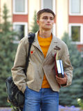 Student with backpack and books in hands. Student walks with book bag and books in hand Stock Photo