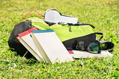 Student backpack with glasses, books and headphones. Student backpack with some books scatered around, glasses and headphones on a meadow royalty free stock photography