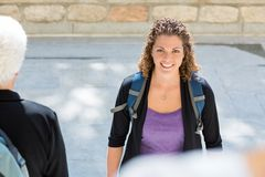 Student With Backpack Standing On College Campus. Portrait of smiling mid adult student with backpack standing on college campus Stock Photography