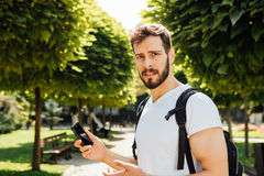 Student with backpack talking at cellphone Royalty Free Stock Images