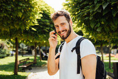 Student with backpack talking at cellphone Royalty Free Stock Image