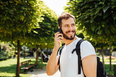 Student with backpack talking at cellphone stock image
