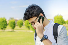 Student with bag talking in phone,outdoor. Stock Photography