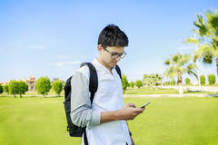 Student with bag talking in phone,outdoor. Royalty Free Stock Photography