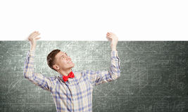 Student with banner. Young man with white blank banner. Place for text Stock Photos