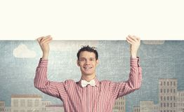Student with banner. Young man with white blank banner. Place for text Royalty Free Stock Photos