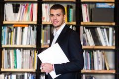 Student in bibliotheek De knappe boeken van de jonge mensenholding en het glimlachen terwijl status in bibliotheek Royalty-vrije Stock Afbeelding