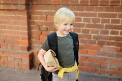 Student with big backpack and lunch bag near the school building. Back to school royalty free stock images