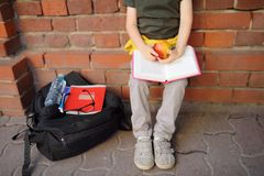 Student with big backpack and lunch bag sat down to eat his lunch near the school building. School meals. Back to school royalty free stock images