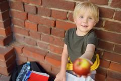 Student with big backpack and lunch bag shares his apple near the school building. School meals. Back to school royalty free stock images