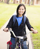 Student with Bike. Portrait of an attractive Asian  female student posing by a bike Royalty Free Stock Image