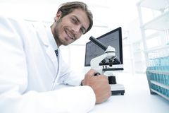 Student in biology using microscope in training class. Close-up portrait of a male scientific researcher using microscope in the laboratory Stock Images