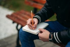 A student in a black jacket sits in a park on a bench writes down his thoughts in a notebook. Handsome boy.  Stock Image