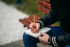 A student in a black jacket sits in a park on a bench writes down his thoughts in a notebook. Handsome boy.  Royalty Free Stock Photos