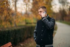 A student in a black jacket sits in a park on a bench and use the phone. Handsome boy. A student in a black jacket sits in a park on a bench writes down his Stock Photo
