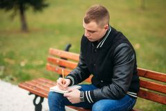 A student in a black jacket sits in a park on a bench writes down his thoughts in a notebook. Handsome boy.  Stock Photo