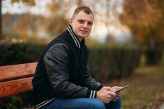 A student in a black jacket sits in a park on the bench and use tablet. Handsome boy. A student in a black jacket sits in a park on a bench writes down his Royalty Free Stock Photography