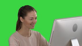 Student blonde girl looking at monitor of computer and smiling on a Green Screen, Chroma Key. Close up. Student blonde girl looking at monitor of computer and stock video